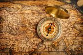 Old vintage retro golden compass on ancient map. The map used for background is in Public domain. Ma
