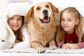 foto of prone  - Little sisters and pet dog having fun at home - JPG