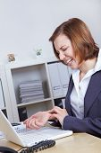 Woman with computer in office with arthritis in her hand wrist