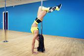 Pole Fitness. Professional Poledancer Exercising In Dance Class. The Recliner Pose Performed By Youn poster