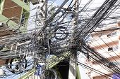 Messy Wires Attached To The Electric Mast. The Chaos Of Cables And Wires On An Electric Pole. Many E poster