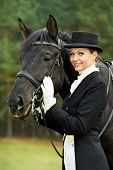 horsewoman jockey in uniform standing with horse outdoors