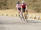 Active male bike riders riding cycles on a country road