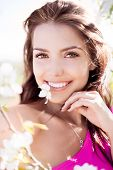 beautiful young brunette woman with a flower in her teeth standing near the apple tree on a warm sum