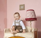 little child baby boy sitting on the floor indoors in babyroom smiling happy