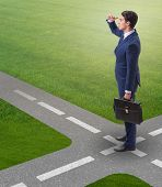 The young businessman at crossroads in uncertainty concept poster
