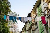 Multi-colored Laundry On A Rope High In The Air. Sochi Authenticity. Green Tree And Prefabricated Ho poster