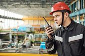 industrial worker on factory with walkie talkie transmitter poster