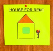 poster about renting the house with the key on wooden background