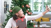 Young Asian Man Smiling While Taking Selfie Photo With Christmas Present Gift Box, Happy Asia Blogge poster