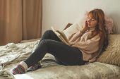Attractive Young Woman Is Reading A Book At Home. Thoughtful Girl Reading Important Book. Reading An poster