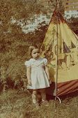 Vintage photo of  little girl and toy wigwam (early eighties)