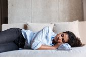 Attractive young african woman relaxing on a couch at home, sleeping with mobile phone on couch poster