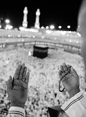 Muslim praying at Makkah holy Islamic place - Kaaba is visible