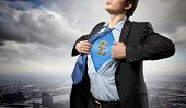 Image of young businessman in superhero suit with pound sign on chest