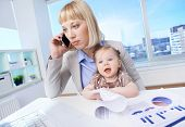Portrait of successful businesswoman at workplace calling with her daughter near by