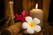 Low light spa setting indoor with candle, frangipani and aroma set.