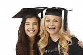 Closeup portrait of beautiful young females in graduation cap smiling happy, hugging.