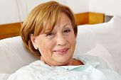 Smiling senior woman sitting in bed in her sleeping room