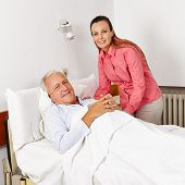Smiling woman visiting old bedridden man in a hospital bed