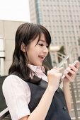 Business woman use smartphone in outside of modern city.