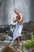 Young handsome man enjoying waterfall in the tropics