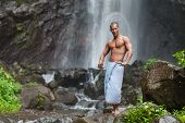 image of qigong  - Young handsome man enjoying waterfall in the tropics - JPG