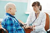médico enfermeira medindo a pressão arterial do paciente pelo estetoscópio no hospital de clínica