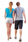 Back view of walking young couple (man and woman) . young husband and wife walk man watches with int