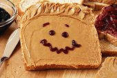 Making peanut butter sandwiches with personality!  Fun smiley face drawn on with jam. Creamy peanut