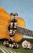 picture of kukui nut  - Closeup of beautiful Hawaiian koa wood ukulele with abalone inlay on a palm frond draped with kukuinut lei and a seashell on blue backgound - JPG