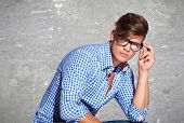Fashion young man holding his fashionable glasses on gray background
