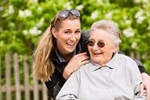 image of granddaughter  - Young woman is visiting her grandmother in nursing home having a walk with here in a wheelchair - JPG