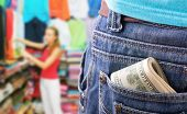 Closeup of money in the pocket against girl at clothing store