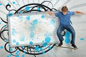 Skateboarder mid ollie in front of copy space screen with blue paint splashes and black decorative f