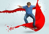 Skateboarder mid ollie with red paint splash detail on pale blue background
