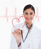 Happy doctor holding up stethoscope to red heart design on ECG line background