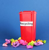 Recycling bin with papers on blue background