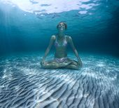 Young woman sitting on a sea sandy bottom in lotus position and holding a breath