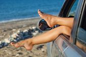Woman's legs are dangling out a car window