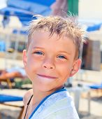 Smiley seven years old boy on the beach with towel