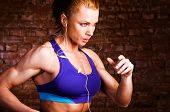 picture of cardio exercise  - strong woman is running and listening music - JPG