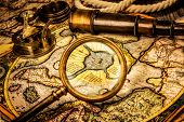 Vintage magnifying glass, compass, telescope lies on the ancient map of the North Pole (also Hyperborea). Arctic continent on the Gerardus Mercator map of 1595.
