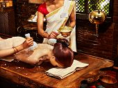 image of panchakarma  - Woman having ayurvedic massage with pouch of rice - JPG