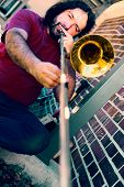 man trombonist plays music on a city street