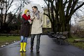 stock photo of rainy day  - Young couple in love having a walk in the park on a rainy day - JPG