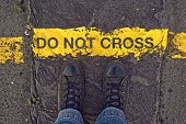 picture of pedestrian crossing  - Male sneakers on the asphalt road with yellow line and title Do Not Cross - JPG