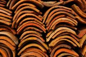 stock photo of roof tile  - Closeup of piles of very old clay rooftop tiles - JPG