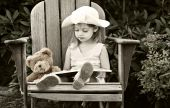 stock photo of storytime  - Vintage style image of a child reading to her teddy bear - JPG