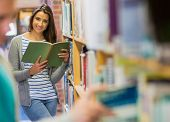 Portrait of a young smiling student reading a book by bookshelf in the library